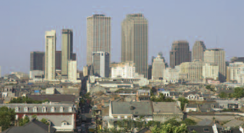 Downtown New Orleans rises behind the French Quarter, as seen from a rooftop of the Bywater area. The St. Louis Cathedral is in the center.