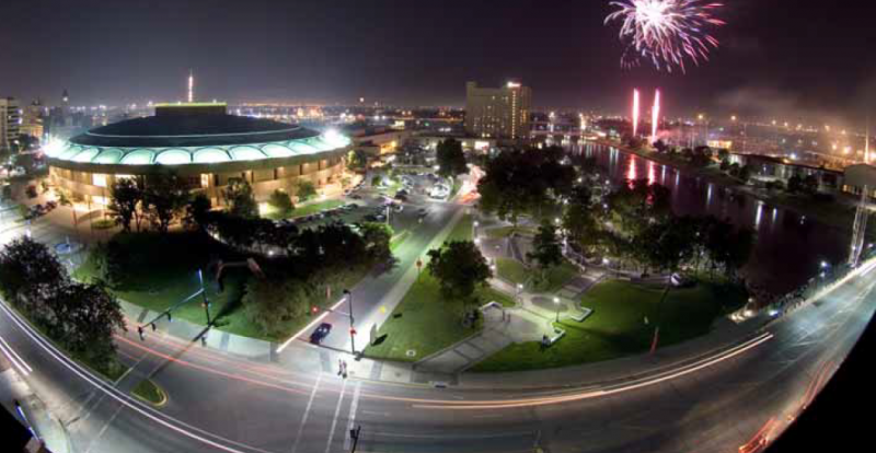 Fireworks reflect in the Arkansas River in downtown Wichita during a July 4th celebration. The Century II Performing Arts & Convention Center is at left, and the Hyatt Regency Wichita is in the center.