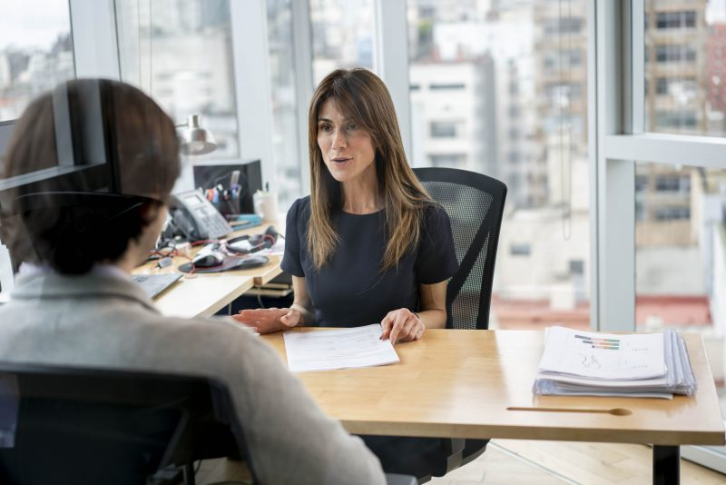 HR manager at her office talking to employee cheerfully