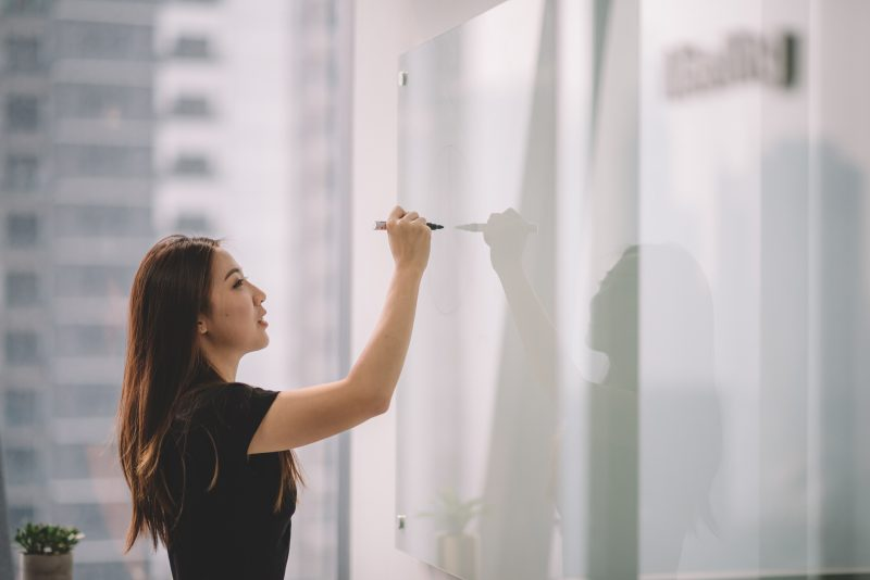 an asian chinese female writing on white board with her marker pen during conference meeting in office conference room