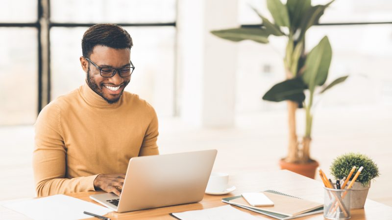 Headshot of handsome black guy using laptop